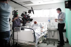 Film set with man laying on hospital bed.