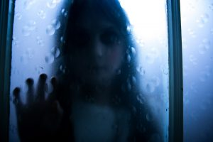 Exorcist girl putting hand onto frosted window.