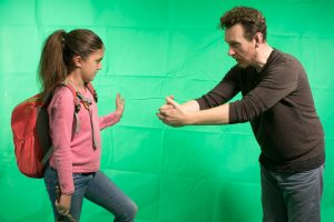 Man directing girl for creative green screen filming
