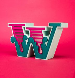 Ben Eine letter W sculpture on a pink background.